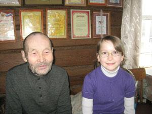 Дедушка Терентий и Ксюша на фоне грамот